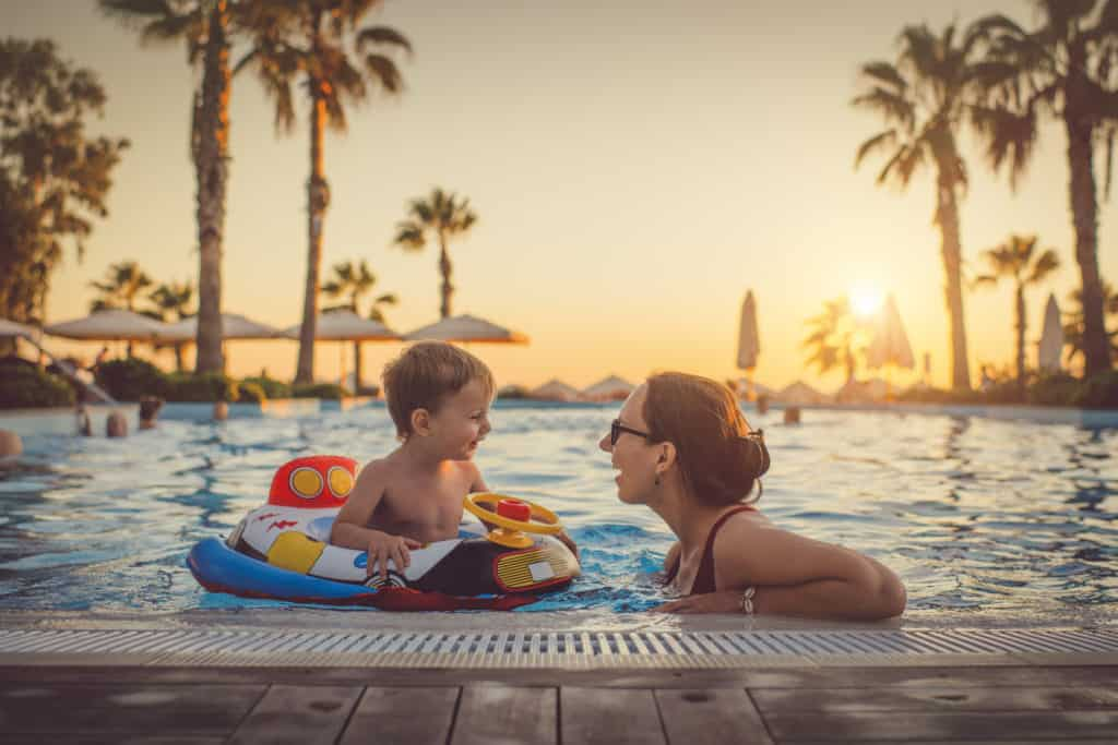 Child with mother in swimming pool, holiday resort