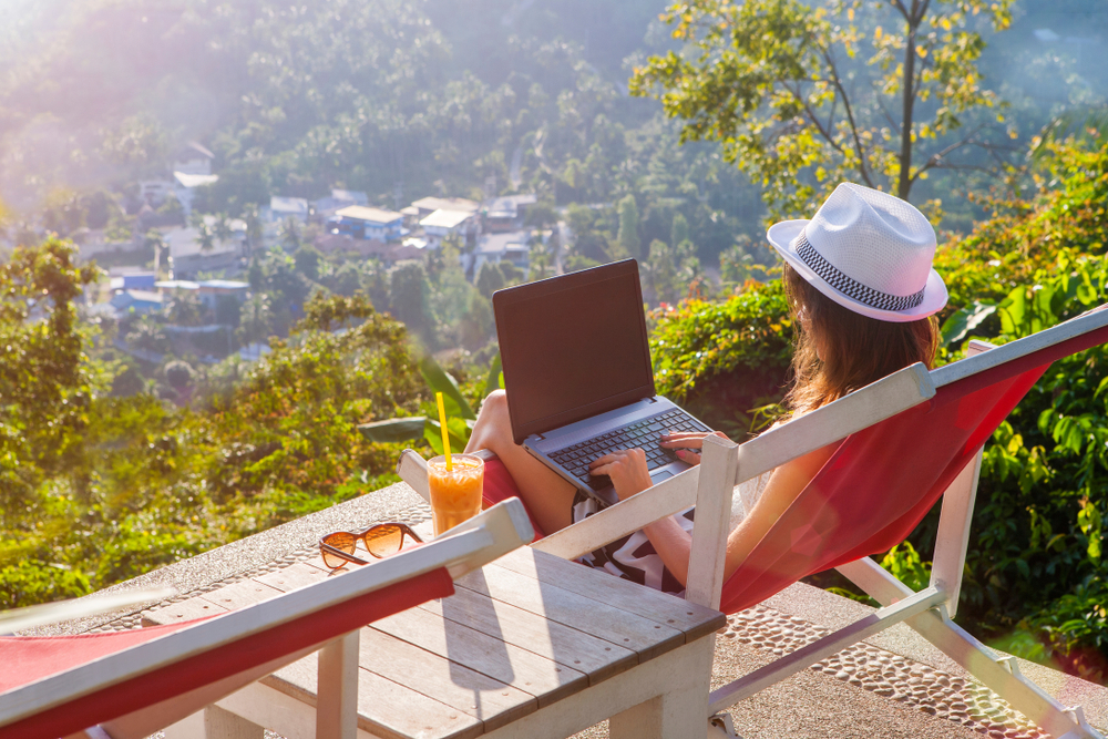 Girl freelancer typing on laptop and looking at monitor with beautiful view
