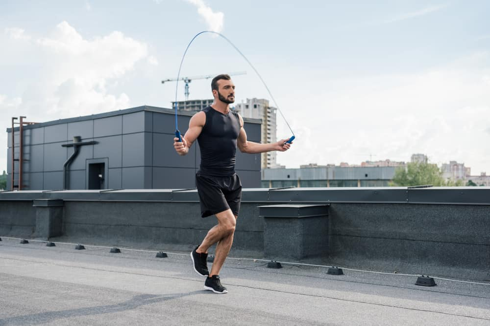 Man jumping rope on a roof top