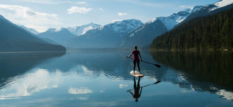 Woman stand up paddle boarding on a pristine lake on a cheap vacation