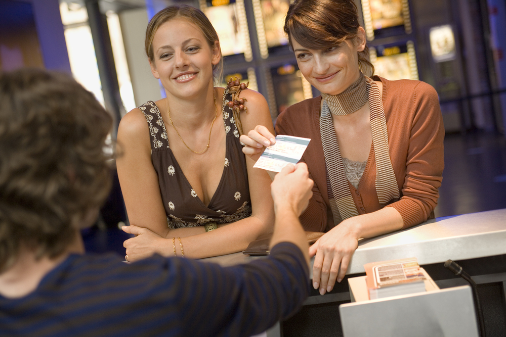 Women buying movie tickets at the box office
