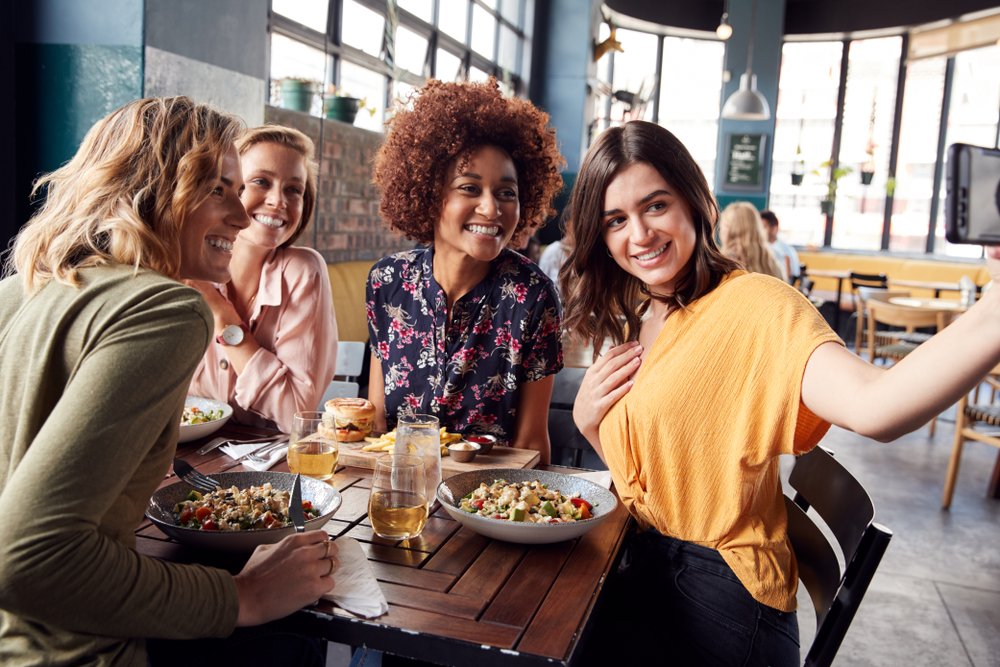 Women enjoying a meal in a top country for happiness