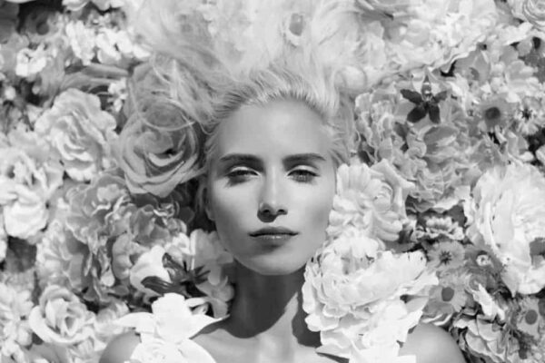 photo-of-beautiful-young-woman-lying-in-flowers