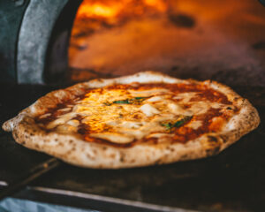 pizza by a wood-burning oven