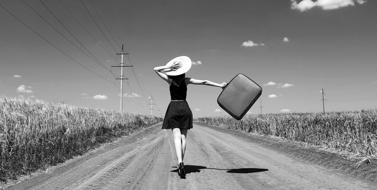 woman running down road with suitcase